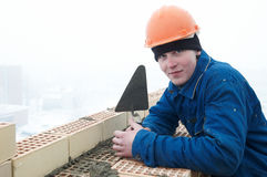Brick layer worker builder mason. A brick layer worker building a brick wall at construction site Stock Photos