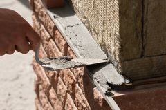 Laying of facing brick over mineral insulation. Brick laying on top of a mineral insulation close-up stock image