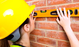 Brick Level. A young female in a hard hat checking if brick wall is level Stock Photos