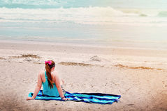A young teenage girl sitting on beach towel looking at ocean. Royalty Free Stock Image