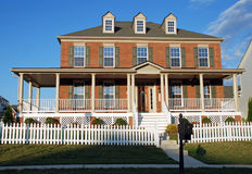 Brick Luxury Home 24. Large luxury home with white picket fence,  brick facade, wrap around porch and green shutters Royalty Free Stock Image