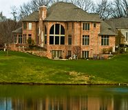 Brick luxury home golf course. A luxury brick home on a golf course with an artifical lake in front of it royalty free stock images