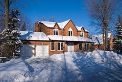Brick luxury house in winter. Large brick house with double garage against deep blue sky in winter Royalty Free Stock Photo