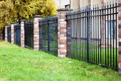 Brick and metal fence royalty free stock photography