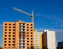 Brick multistory building under construction with crane on the site, blue sky background royalty free stock photo