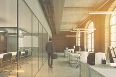 Brick office, arch windows, computers front, man. Open space office with brick and glass walls, a concrete floor and big windows. A row of computer desks Royalty Free Stock Photos