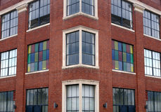 Brick Office Building. Corner old brick office building with colorful windows royalty free stock image