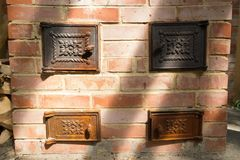 Oven of red brick with cast iron doors close up. A brick oven with cast iron doors close up. cast iron doors with pattern Stock Photography