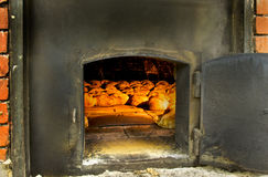 Brick oven cooking bread. Traditional brick oven . Ideal for Bread and pizza . We can see the bread cooking inside Royalty Free Stock Image