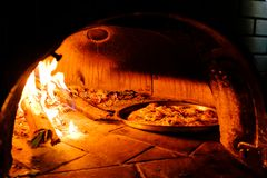 Brick oven with hot pizza cooking inside. Brick oven with hot homemade pizza cooking inside Royalty Free Stock Images