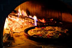 Brick oven with hot pizza cooking inside. Brick oven with hot homemade pizza cooking inside Stock Photos