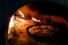 Brick oven with hot pizza cooking inside. Brick oven with hot homemade pizza cooking inside Stock Image