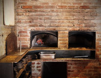Brick Oven Kitchen. A traditional brick oven with glowing, hot, red coals in a restaurant kitchen with many pans and other cooking implements Royalty Free Stock Images