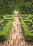 Brick pathway in formal garden. A brick pathway in a formal garden setting with low hedges and surrounding borders Royalty Free Stock Photo