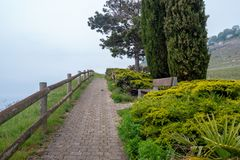 Brick pathway with wooden rail at viewpoint in rural area of Switzerland on cloudy sky background royalty free stock photos
