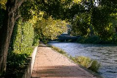 Fall walk next to river. Brick paved walk in autumn next to river covered by trees Stock Photo