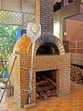 Brick Pizza Oven with Pizza Peel and Firewood. Closeup Brick Pizza Oven with Pizza Peel and Firewood Stock Images
