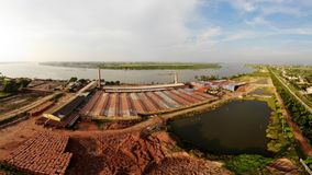 Brick production village stretches along the river bank stock image