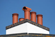 Brick Red Chimney Pots. On a white painted stack, against a blue cloudless sky Royalty Free Stock Image