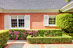 Brick red house with English garden and white window shutters. Stock Photos