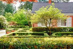 Brick red house with English garden and white window shutters. Stock Photo