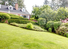 Free Brick Red House With English Garden And White Window Shutters. Royalty Free Stock Photos - 30607738
