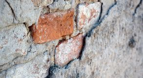 A brick. A red brick in a very old and dirty wall Stock Image