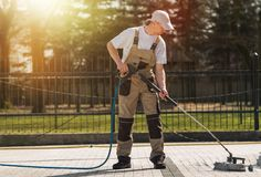 Brick Road Cleaning by Pro. Brick Residential Roadway Cleaning by Professional Cleaning Worker. High Pressure Water Mechanical Brick and Pavements Cleaning Stock Images