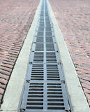 Brick road and grate. A brick road abtract blur with a metal grate drain down the center Stock Photography