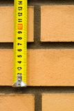 Brick and ruler. Measuring ruler on a background of a brick wall Royalty Free Stock Image