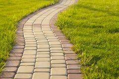 Brick Sidewalk. Garden stone path with grass growing up between and around stones, Brick Sidewalk Stock Photos