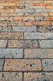 Brick Sidewalk. Tar speckled orange and grey brick sidewalk, background and texture Stock Photography