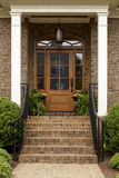 Brick staircase leading up to a brown front door Stock Photo