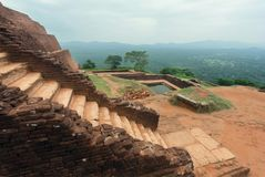 Brick stairs of historical city Sigiriya, ancient landscape, water pool and trees, Sri Lanka. UNESCO world heritage site Stock Photo