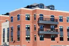 Brick and stone apartment building with outdoor patios. Interesting architecture of contemporary brick and stone apartment building with outdoor patios in busy Royalty Free Stock Photography