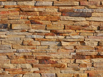 Brick stone fence background. Brick stone bumpy fence background in warm sunset light royalty free stock image
