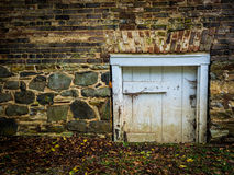 Brick and Stone Wall with Small Wooden Door Royalty Free Stock Photo