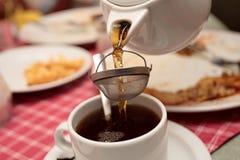 Brick tea. Pouring brick tea in a teacup in restaurant Stock Photos