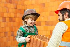 Brick. Team of builders. Building a new home. Father and son at a construction site. stock photography
