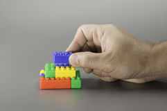 Brick toy and hand Stock Images