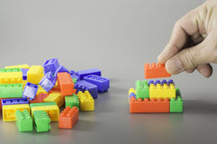 Brick toys and hand Royalty Free Stock Photography