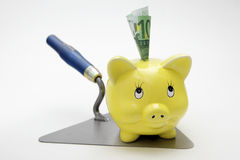 Brick trowel with piggy bank Stock Photos