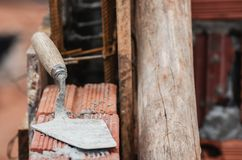 Brick trowel tool over a masonry wall. C. Onstruction background royalty free stock photography