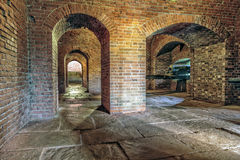 Brick Underground Artillery Tunnel. Historic brick archway and tunnel. Antique artillery cannon points out of window Royalty Free Stock Image