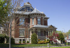 Brick Victorian Home. Stately brick Victorian style home in Webb City, Missouri.  Beautifully manicured front yard with ornate iron fencing Royalty Free Stock Photo