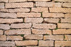 Brick vintage wall plastered with a stone close up / Part of architectural background, rustic materials and texture detail.  royalty free stock image