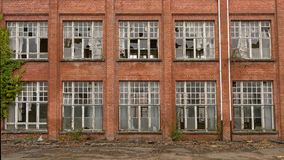 Brick wall with broken windows of an abandoned school. Brick wall with broken windows of an old abandoned school building royalty free stock photos