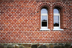 Brick wal. Red brick wall with some windows Royalty Free Stock Images