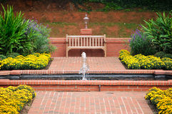 Brick Walkway and Garden Water Fountain Bench. Beautiful Red Brick Walkway and Flower Garden with Water Fountain and Wooden Bench Stock Photo