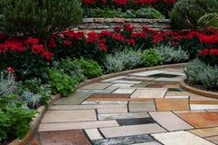 Brick walkway indoor garden red poinsettias greenery. Brick walkway indoor garden red poinsettias green plants royalty free stock images